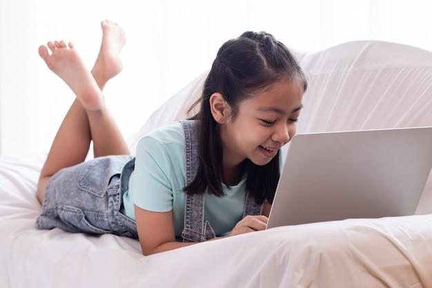 Junges kleines asiatisches mädchen legen sich zu hause mit glücklichem spielendem spiel hin oder erledigen hausaufgaben