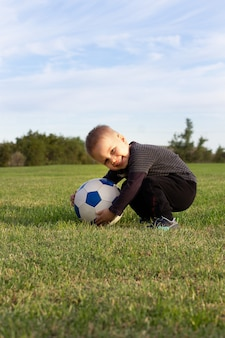 Junges kleines kind 3 jahre alt, das glückliches fußballspielen im grasstadtparkfeld genießt