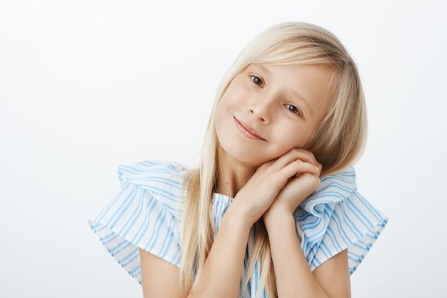 Junges kleines mädchen, das entzückendes gesicht macht, um zu bekommen, was will. erfreutes fürsorgliches kleines kind mit blonden haaren, breit lächelnd, auf schulter gestützt und hände nahe gesicht mit engelsausdruck und lächeln haltend