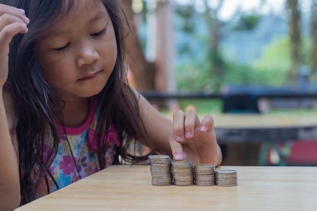 Junges kleines mädchen, das münzen betrachtet