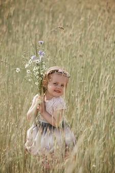 Junges kleines mädchen mit dem langen haar, weißes kleid einsam gehend auf dem mohnblumengebiet und blumen für einen blumenstrauß sammelnd