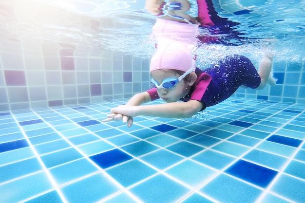 Junges kleines nettes unterwassermädchen schwimmt im swimmingpool mit ihrem schwimmlehrer.