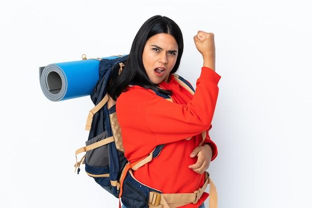 Junges kolumbianisches bergsteigermädchen mit einem großen rucksack auf weißer wand, die starke geste macht