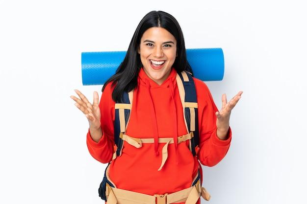 Junges kolumbianisches bergsteigermädchen mit einem großen rucksack auf weißer wand unglücklich und frustriert mit etwas