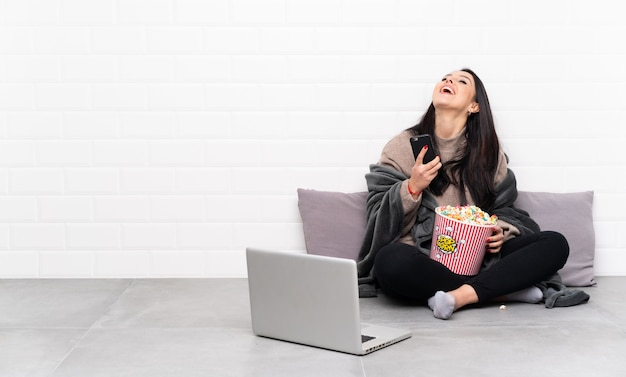 Junges kolumbianisches mädchen, das eine schüssel popcorn hält und einen film in einem laptop mit telefon in der siegposition zeigt