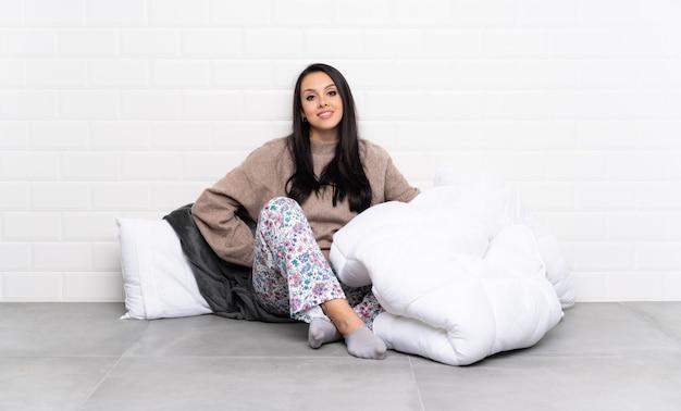 Junges kolumbianisches mädchen in den pyjamas am zuhause lachen