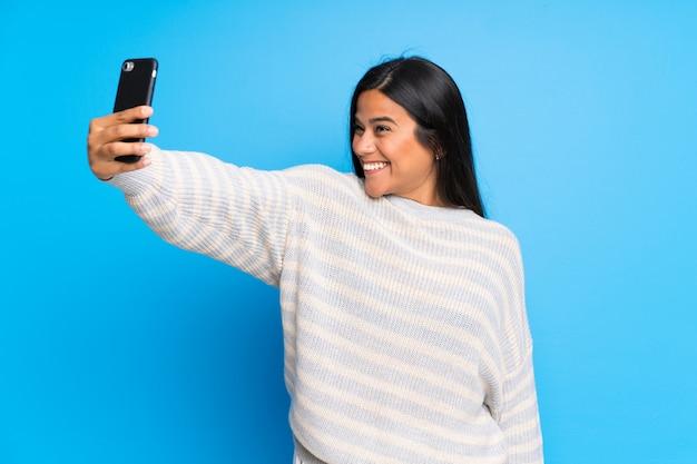 Junges kolumbianisches mädchen mit der strickjacke, die ein selfie macht