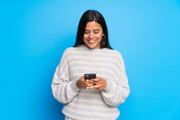 Junges kolumbianisches mädchen mit der strickjacke, die eine mitteilung mit dem mobile sendet