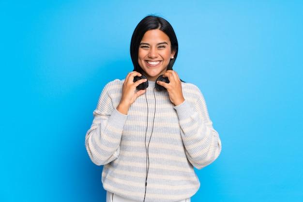 Junges kolumbianisches mädchen mit strickjacke mit kopfhörern
