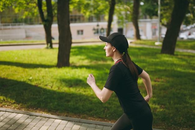 Junges, konzentriertes, sportliches, schönes brünettes mädchen in schwarzer uniform und mütze, das sportübungen macht und im freien gerade auf dem weg im stadtpark schaut