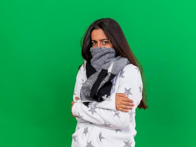Junges krankes mädchen, das das tragen der kamera und das bedeckte gesicht mit dem eiskalten schal lokalisiert betrachtet, lokalisiert auf grünem hintergrund