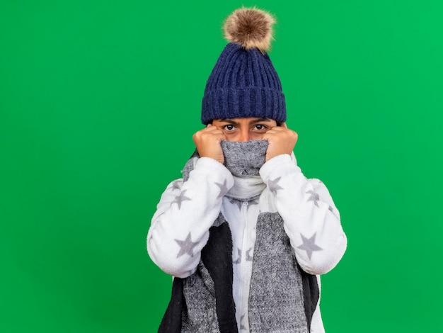 Junges krankes mädchen, das kamera betrachtet, die wintermütze mit schal und bedecktem gesicht mit schal lokalisiert auf grünem hintergrund mit kopienraum betrachtet