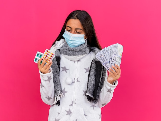 Junges krankes mädchen, das medizinische maske mit schal hält, der geld hält und pillen in ihrer hand lokalisiert auf rosa betrachtet