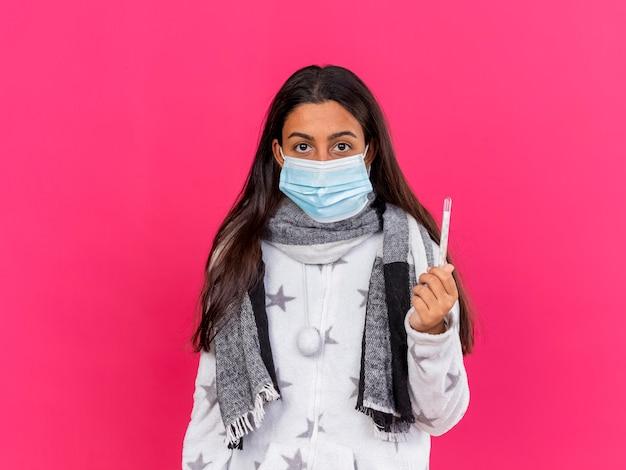 Junges krankes mädchen, das medizinische maske mit schal hält thermometer auf rosa isoliert trägt