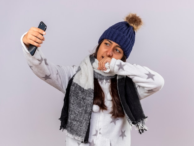 Junges krankes mädchen, das wintermütze mit schal trägt, nehmen ein selfie lokalisiert auf weißem hintergrund