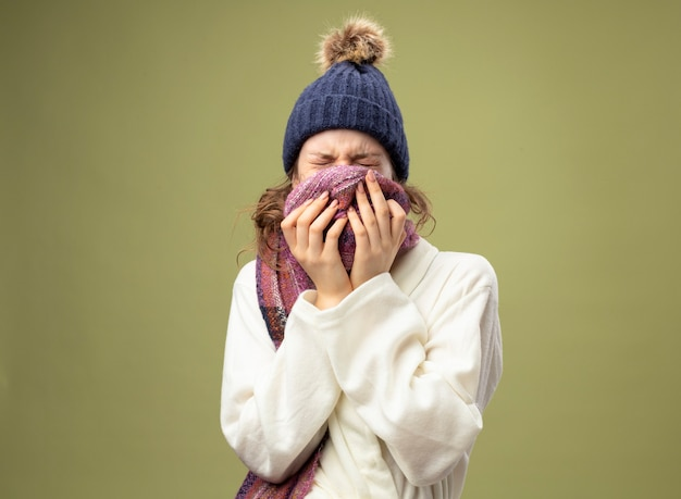 Junges krankes mädchen mit geschlossenen augen, die weiße robe und wintermütze mit schal bedeckten gesicht mit schal tragen
