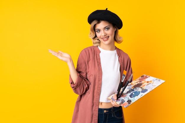 Junges künstlermädchen, das eine palette lokalisiert auf gelber wand hält, die auf der handfläche imaginären copyspace hält
