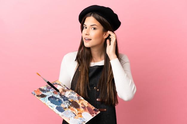Junges künstlermädchen, das eine palette über isoliertem rosa hintergrund hält und etwas hört, indem es die hand auf das ohr legt