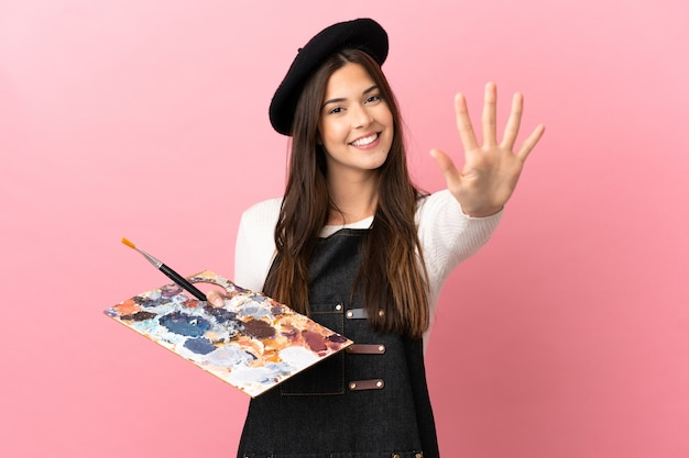 Junges künstlermädchen, das eine palette über isoliertem rosa hintergrund hält und fünf mit den fingern zählt