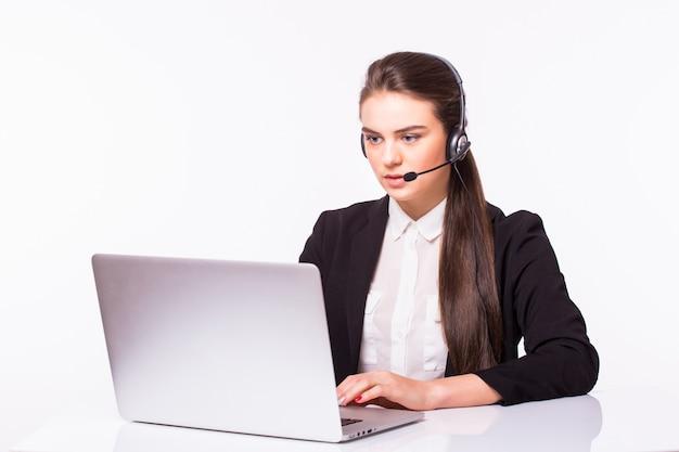 Junges kundendienstmädchen mit einem headset an ihrem arbeitsplatz lokalisiert auf weißer wand