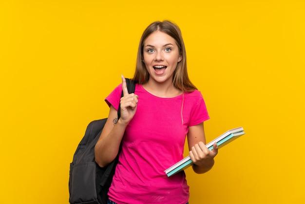 Junges kursteilnehmermädchen über getrennter gelber wand eine großartige idee oben zeigend