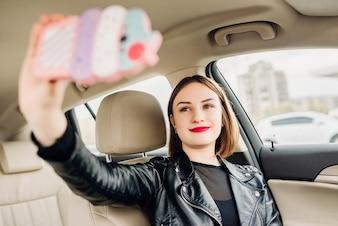 Junges lächelndes gril, das das selfie Porträt sitzt im Auto macht