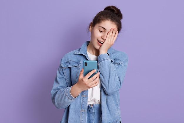 Junges lachendes brünettes teenager-mädchen mit haarknoten, das smartphone in händen hält und die hälfte des gesichts mit handfläche bedeckt