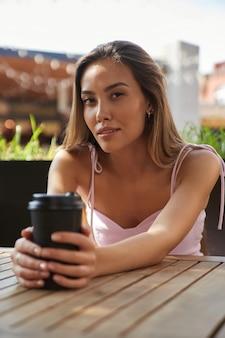 Junges lächelndes asiatisches mädchen in hellem kleid, das auf der caféveranda sitzt und kaffee trinkt