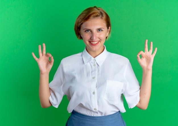 Junges lächelndes blondes russisches mädchen gestikuliert ok handzeichen mit zwei händen