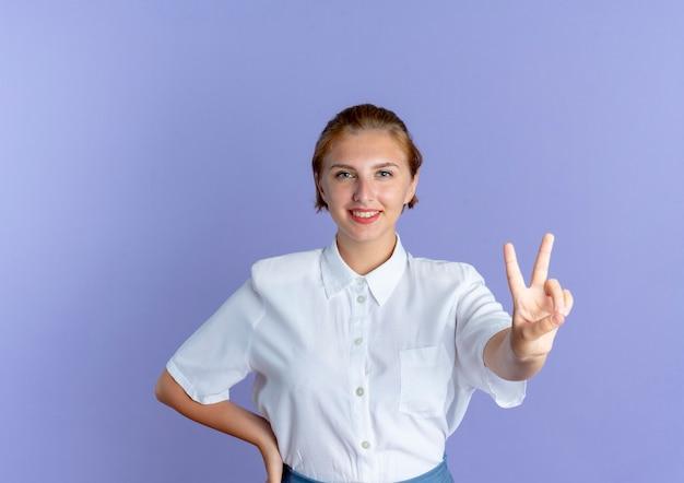 Junges lächelndes blondes russisches mädchen gestikuliert siegeshandzeichen setzt hand auf taille lokalisiert auf lila hintergrund mit kopienraum