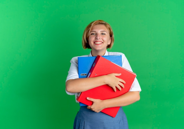 Junges lächelndes blondes russisches mädchen hält dateiordner lokalisiert auf grünem hintergrund mit kopienraum