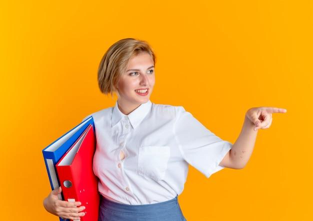 Junges lächelndes blondes russisches mädchen hält dateiordner und punkte seitlich lokalisiert auf orange hintergrund mit kopienraum