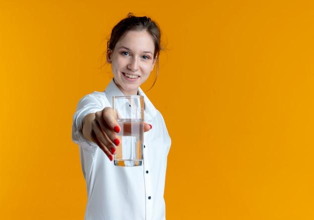 Junges lächelndes blondes russisches mädchen hält glas wasser heraus, das auf orange raum mit kopienraum isoliert wird