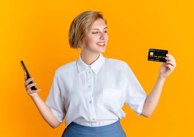 Junges lächelndes blondes russisches mädchen hält telefon und schaut auf kreditkarte