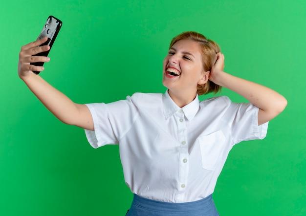 Junges lächelndes blondes russisches mädchen schaut auf telefon, das selfie nimmt, legt hand auf kopf