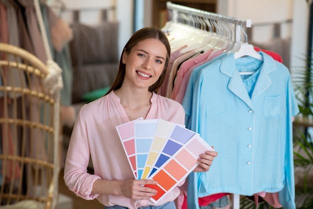 Junges lächelndes designermädchen mit farbskalen in ihren händen