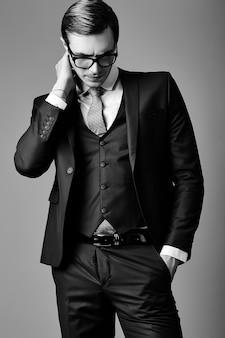 Junges lächelndes elegantes hübsches männliches geschäftsmannmodell in einem anzug und in den modischen gläsern, die im studio aufwerfen