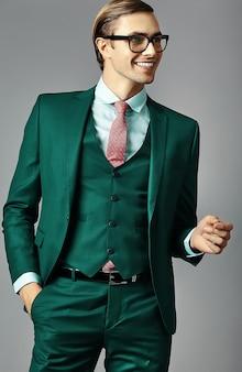 Junges lächelndes elegantes hübsches männliches geschäftsmannmodell in einem anzug und in den modischen gläsern