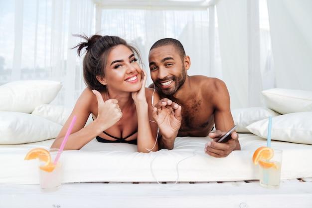 Junges lächelndes glückliches paar, das auf dem strandbett liegt und okay zeichen zeigt
