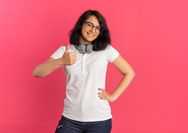 Junges lächelndes hübsches kaukasisches schulmädchen, das brille und kopfhörer am hals daumen hoch trägt und hand auf taille auf rosa mit kopienraum legt