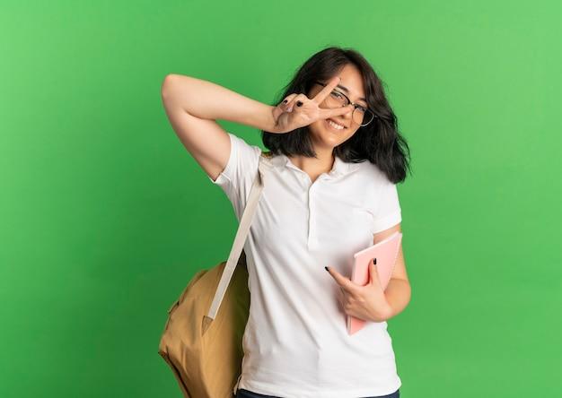 Junges lächelndes hübsches kaukasisches schulmädchen, das brille und rückentasche trägt, gestikuliert sieghandzeichen, das notizbuch auf grün mit kopienraum hält