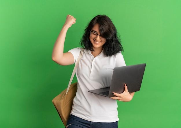 Junges lächelndes hübsches kaukasisches schulmädchen, das brille und rückentasche trägt, hält laptop, der faust auf grün mit kopienraum erhebt