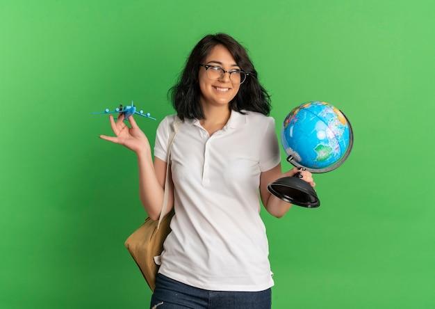Junges lächelndes hübsches kaukasisches schulmädchen, das brille und rückentasche trägt, hält spielzeugflugzeug und globus auf grün mit kopienraum