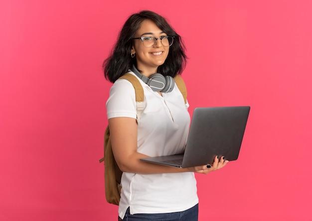Junges lächelndes hübsches kaukasisches schulmädchen mit kopfhörern am hals, das brille und rückentasche trägt, hält laptop auf rosa mit kopienraum