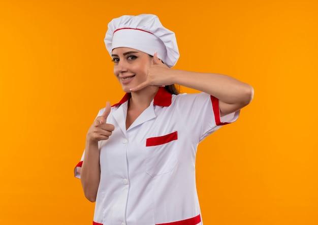 Junges lächelndes kaukasisches kochmädchen in den einheitlichen gesten des kochs nennen mich handzeichen lokalisiert auf orange wand mit kopienraum