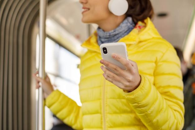 Junges lächelndes mädchen bei der stellung im zug, in der tram oder im bus. glücklicher weiblicher passagier, der öffentlich musik auf einem transport des smartphone hört.