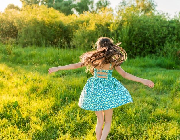 Junges lächelndes mädchen, das im sommer auf wiese tanzt