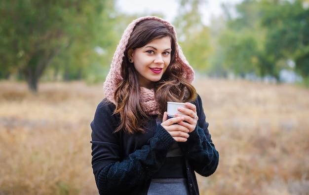 Junges lächelndes mädchen in einem schal und einer mütze mit einer tasse kaffee (tee) in den händen des herbstes draußen.