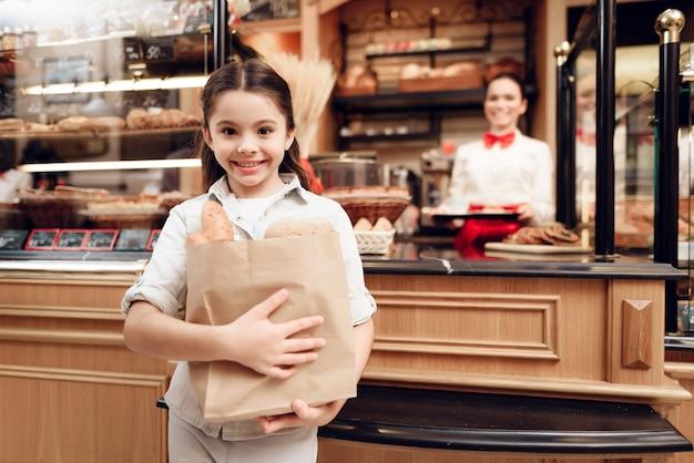 Junges lächelndes mädchen-kaufendes brot in der modernen bäckerei.