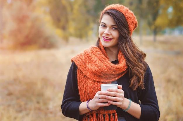 Junges lächelndes mädchen mit einer tasse kaffee (tee) für einen spaziergang im park im freien. herbstwetter. die sonnenstrahlen beleuchten das modell von hinten.